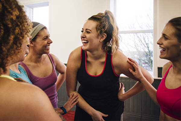 Group of women laughing and talking in exercise class.