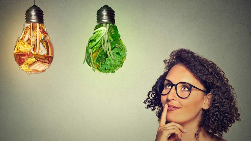 Woman thinking healthy food or junk food in lightbulbs.