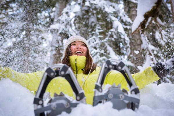 woman throwing snow in air during snowshoe adventure