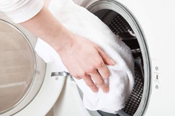 Woman hands loading towels into washing machine.