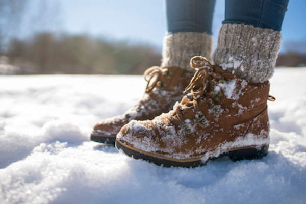 woman wearing winter boots and fluffy socks in snow.