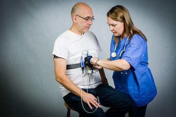 Nurse setting up sleep apnea monitor on male patient.