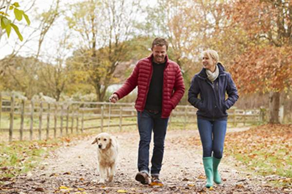 Man and woman taking walk with dog in fall.
