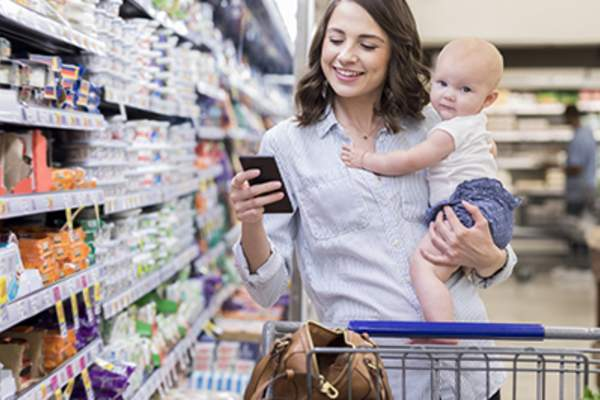 Woman at a grocery store, holding her baby, and checking her period tracking app.