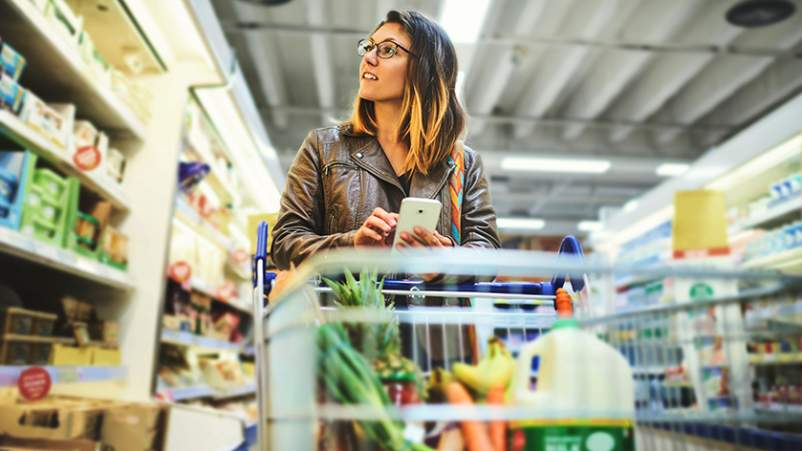 Woman shopping for healthy psoriasis-friendly foods in a grocery store.