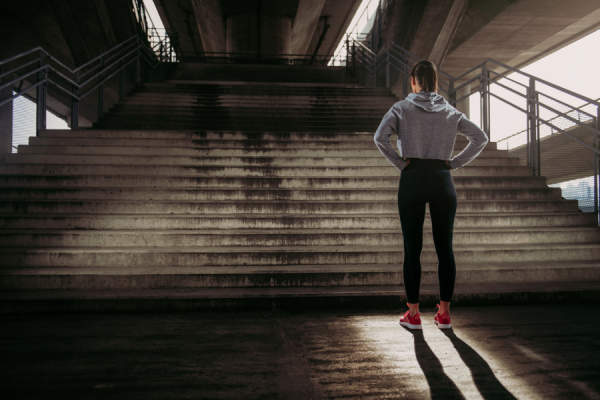 Woman in exercise clothes looking up flight of stairs