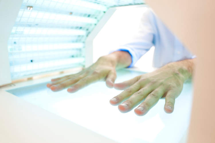 hands in a phototherapy box