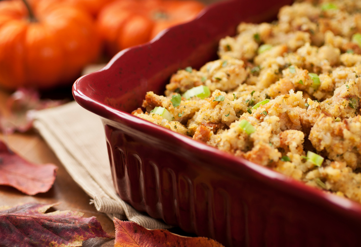 Red dish of Thanksgiving stuffing on table.