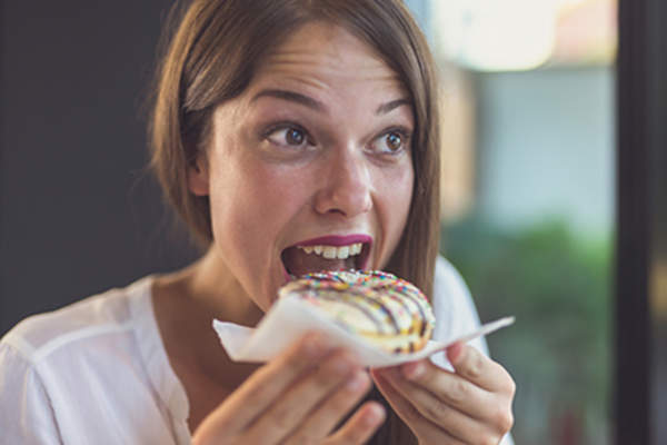 Woman about to eat a doughnut.