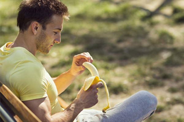Man sitting outside in the sun peeling a banana.