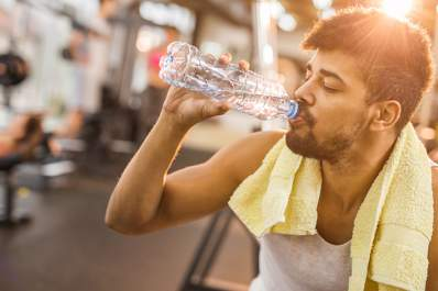 Man drinking water in a gym.