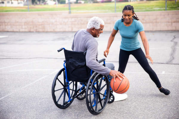 senior man and young woman playing basketball