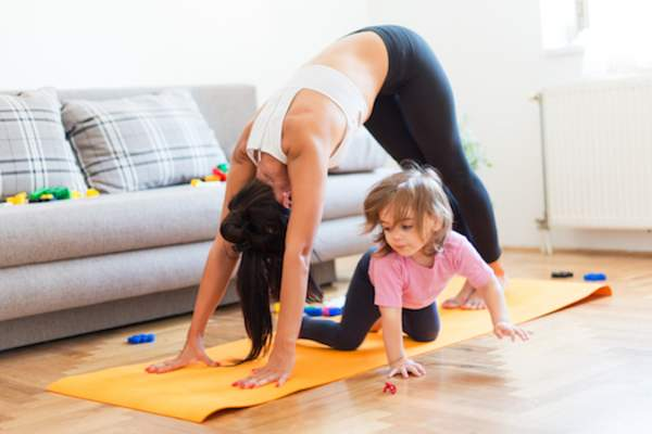 mother exercising while child plays