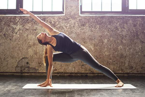 Young woman practicing yoga in an urban loft.