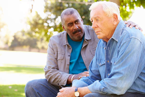 Man Comforting Unhappy Senior Friend Outdoors