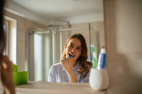 Young woman brushing her teeth in the mirror