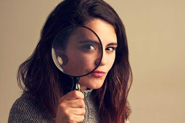 Woman holding a magnifying glass.