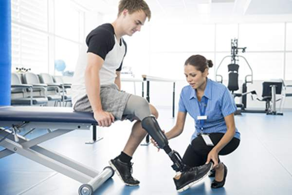 Physical therapist helping man with prosthetic leg.