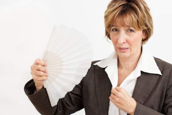 Woman with paper fan suffering hot flash.