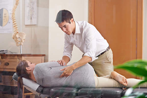 Chiropractor adjusting a woman's spine.