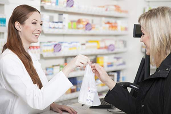 Customer receiving prescription from pharmacist