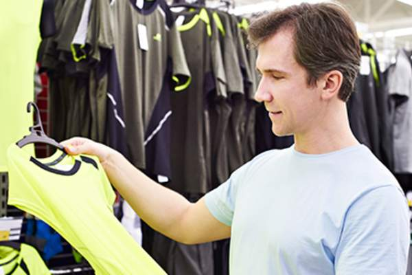 Man shopping for sport t-shirt in a store.