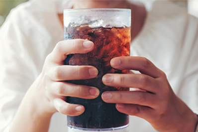 Woman holding a glass of soda or pop.