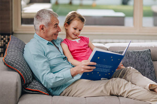 Grandfather reading to young granddaughter on the couch.