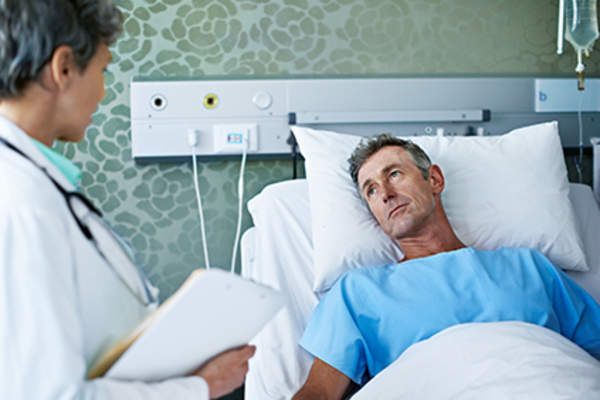Man in a hospital bed talking to a doctor.