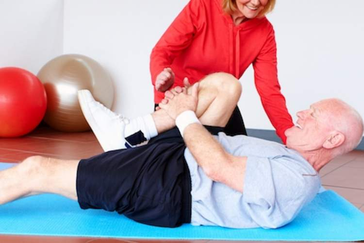 An elderly man works with a physical therapist for back pain.