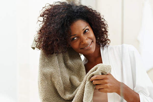 Woman patting her hair dry with a towel.