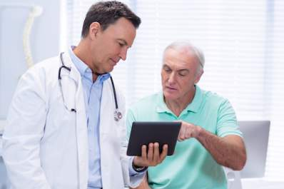 Doctor and patient reviewing treatment options on tablet.