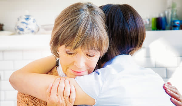 Adult daughter hugging mother who is sad.