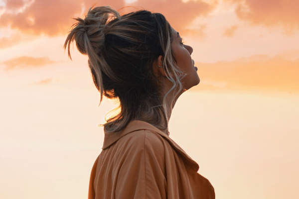 woman looking up at sunset