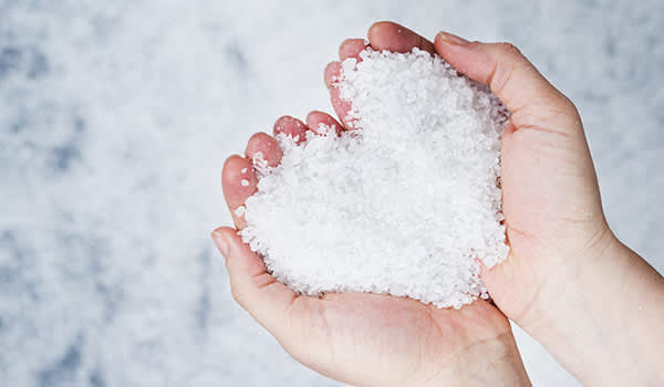 Person holding a heart-shaped pile of salt in their hands.