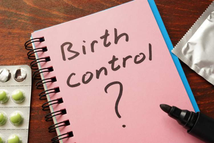"Notebook with ""Birth Control?"" written on it , flanked by a condom and birth control pills."