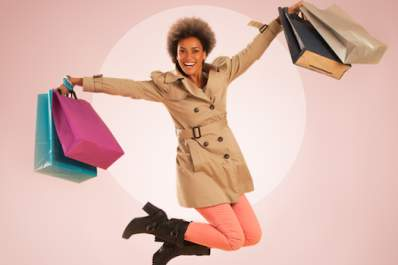 Woman jumping for joy after shopping for fashion.