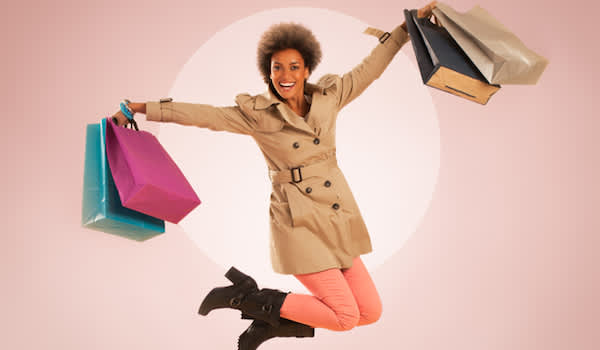 Woman jumping for joy after shopping for ne fashion.