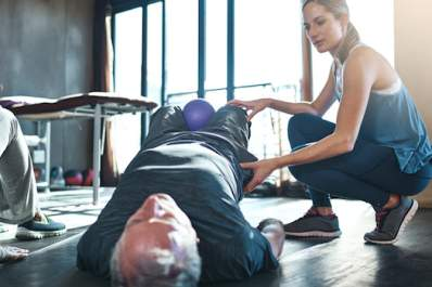 Man does exercises with female physical therapist.