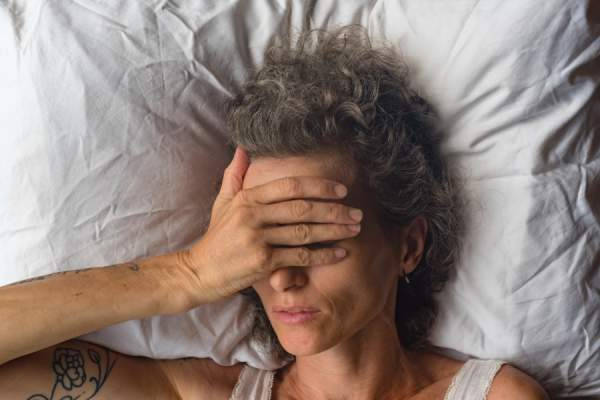 mature woman in bed covering eyes with hand