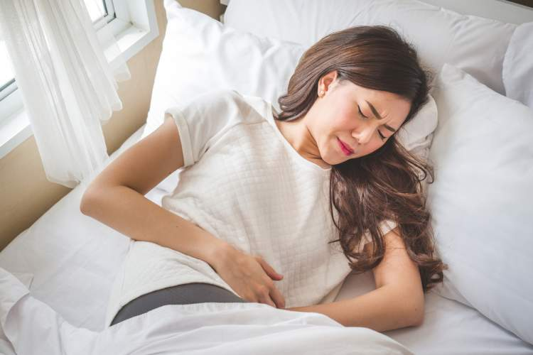 Young woman lying down with severe stomach cramps and pain.