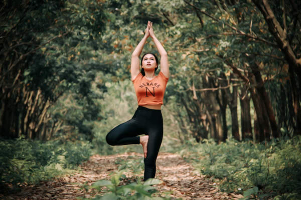 Young woman doing yoga tree pose in the forest