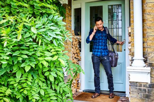 man leaving the house and talking on the phone