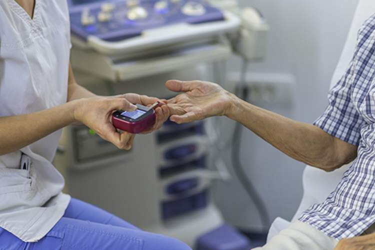 Nurse conducting a blood sugar test on a diabetic patient.