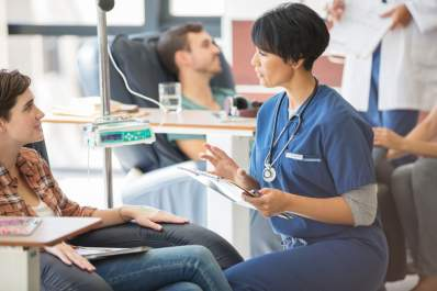 young woman talking to doctor while getting infusion treatment