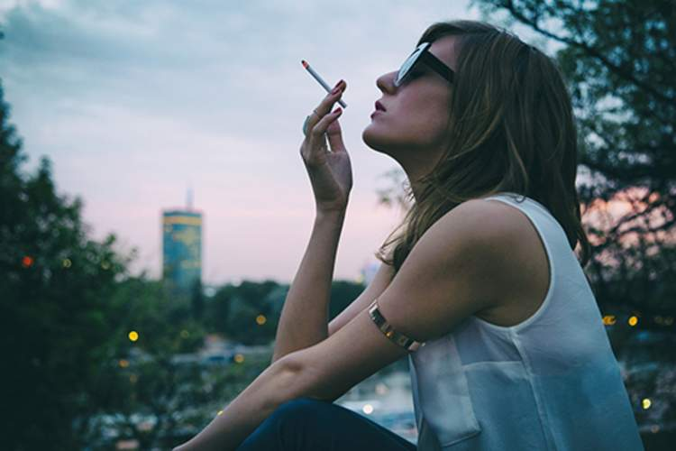 Fashionable woman smoking cigarette outdoors