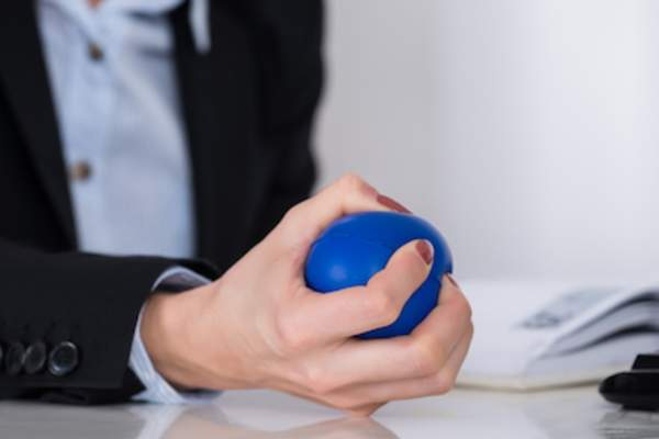 Woman squeezing stress ball.