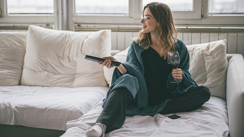 Woman watching TV in pajamas with a glass of wine.
