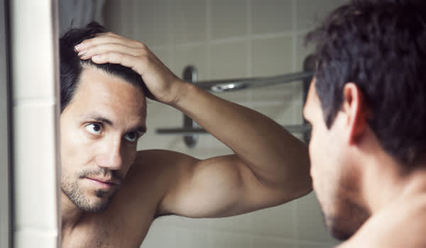 Man checking hair loss in mirror.