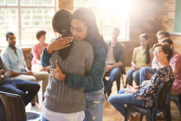 Women hugging in support group